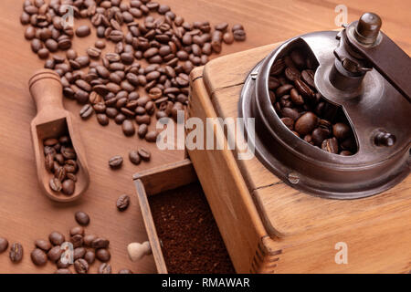 A closeup of a vintage coffee grinder with roasted coffee beans in the blurred background, selective focus - Stock Photo