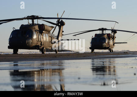 Two U.S. Army UH-60 Black Hawk helicopters of the 1st Combat Aviation Brigade, 1st Infantry Division, were staged on Chièvres Air Base, Jan. 30, 2019. Chièvres Air Base served as an intermediate staging area before the 1st Combat Aviation Brigade deploys to Germany, Poland, Latvia and Romania for nine months to train with NATO partners in support of Atlantic Resolve. (U.S. Army photo by Visual Information Specialist Pascal Demeuldre) - Stock Photo