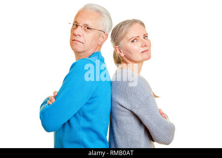 Serious senior couple with crossed arms leaning back to back - Stock Photo