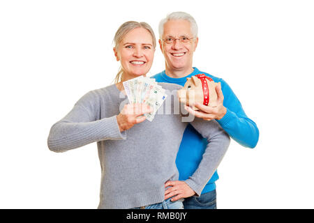 Happy couple of seniors with piggy bank and euro bills in hands - Stock Photo
