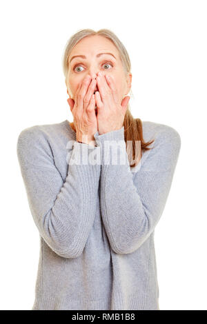 Elderly woman looks surprised and shocked and holds her hand over her mouth - Stock Photo