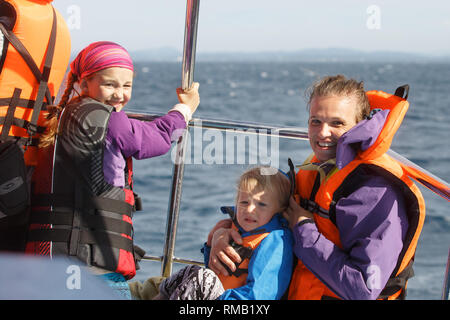 Family on a blue whale watching trip. Smiling girl in safety jacket on a boat trip. Mother holding baby. - Stock Photo