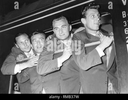 Arrival of the crew at the station in Lindau.Players of the team lean out of the train window. From left: Max Morlock, substitute, Jupp Posipal, Hans Schaefer. In 1954 Germany won its first World Cup in Switzerland. - Stock Photo