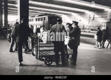 Series of the historical Muenchen Hauptbahnhof, October 1971. Porters with their dolly on the platform. - Stock Photo