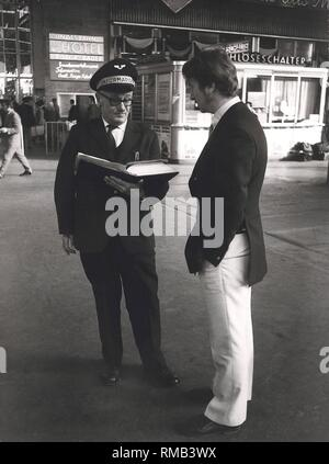 Series of the historical Muenchen Hauptbahnhof, October 1971. Customer service of the railway, an information advisor gives a traveler information. - Stock Photo