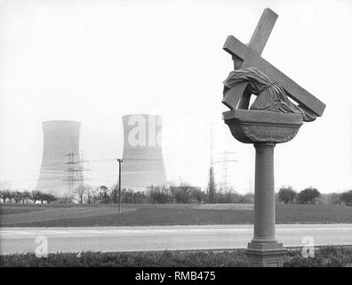 View of the Grafenrheinfeld nuclear power plant. It went into operation in 1982. In the foreground is a wayside cross from the Baroque period. - Stock Photo