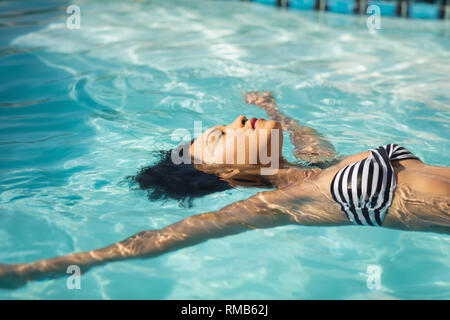 Young mixed-race woman floating in swimming pool