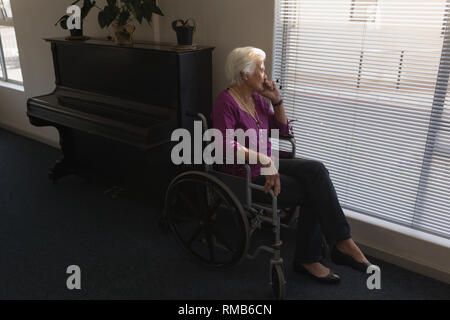 Side view of disabled senior woman sitting on wheelchair and looking outside through window - Stock Photo