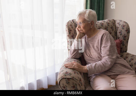 Front view of senior woman sitting on the couch and looking outside through window - Stock Photo