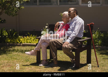 Side view of senior couple relaxing on bench in garden - Stock Photo