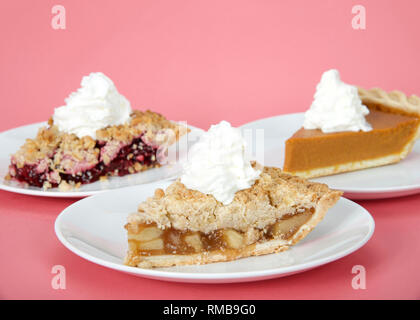 Close up on apple, cherry and pumpkin pie slices on individual plates with whipped cream on top of them on pink background. Focus on front pie, apple. - Stock Photo