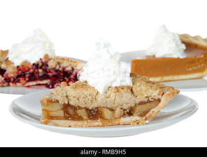 Close up on apple, cherry and pumpkin pie slices on individual plates with whipped cream on top of them, isolated on white. Focus on front pie, apple. - Stock Photo