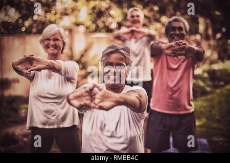 Portrait of senior woman stretching arms with friends - Stock Photo