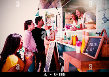 Smiling waiter taking order from couple - Stock Photo