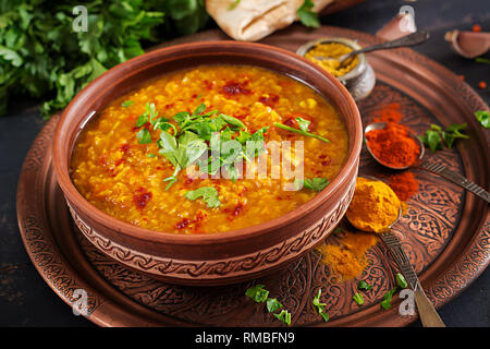 Indian dal. Traditional Indian soup lentils.  Indian Dhal spicy curry in bowl, spices, herbs, rustic black wooden background. Authentic Indian dish. O - Stock Photo