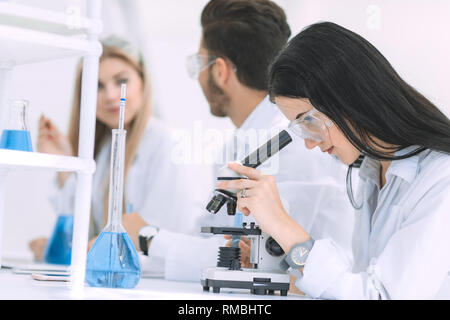 female scientist uses a microscope in the laboratory