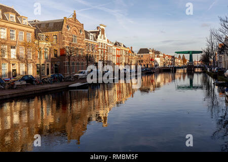 Drawbridge at sunset over a canal in Leiden with classic facades against a blue sky with the scene doubled as a reflection in the water - Stock Photo