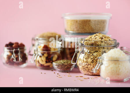 Vegan health food over pink background with copy space. Nuts, seeds, cereals, grains in glass jars. Antioxidants, omega 3, protein and dietary fiber c - Stock Photo