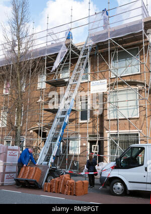 workmen transport roof tiles upwards to insulated roof on apartment building in utrecht - Stock Photo