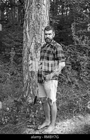Bearded hipster in woods. Brutal lumberjack waiting on path. Barefoot guy standing on ground - Stock Photo