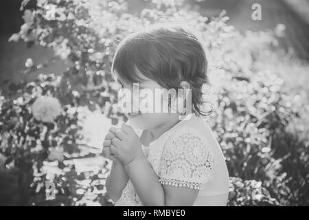 Girl smiling with folded hands in summer garden - Stock Photo