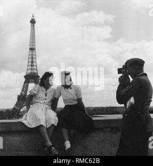 A soldier photographs French civilians in front of the Eiffel Tower. - Stock Photo
