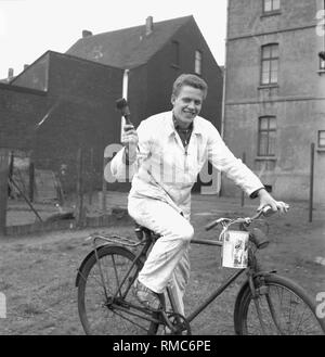 Football coach Otto Rehhagel in his former job as a painter with bicycle and brush in 1960 in Essen. - Stock Photo