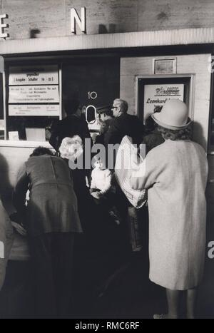 Series of the historical Muenchen Hauptbahnhof, October 1971. Waiting travelers at the ticket office. - Stock Photo