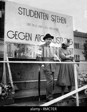 The writer Erich Kaestner attends an anti-nuclear rally outside the University of Munich. In the picture, Kaestner and a student stand in front of a sign reading: 'Students stand day and night against nuclear armaments for three days.' - Stock Photo