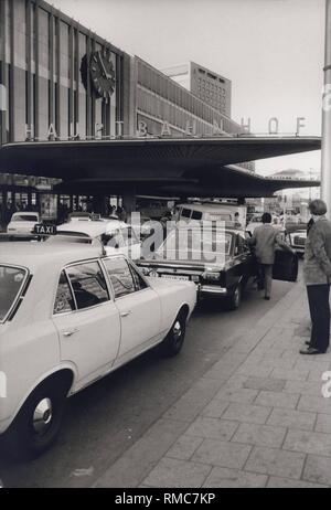 Series of the historical Muenchen Hauptbahnhof, October 1971. Taxi stand at the main entrance, a passenger climbs in. - Stock Photo