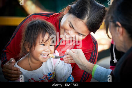 Tonlé Sap Lake,  Cambodia. 19th December, 2017. Happy young girl is being fed from a spoon held by another person while her mother hold her and smiles - Stock Photo