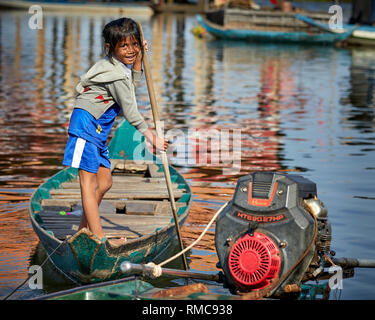 Tonlé Sap Lake,  Cambodia. 19th December, 2017. A young fisherman's daughter on Tonlé Sap Lake stands and rows her wooden boat. - Stock Photo