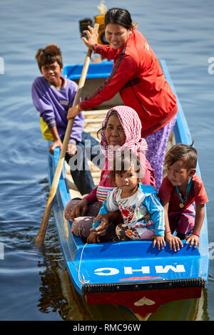 Tonlé Sap Lake,  Cambodia. 19th December, 2017. Women and children ride in their figerglass roat while another woman stands and rows. Photo: BryanWatt - Stock Photo