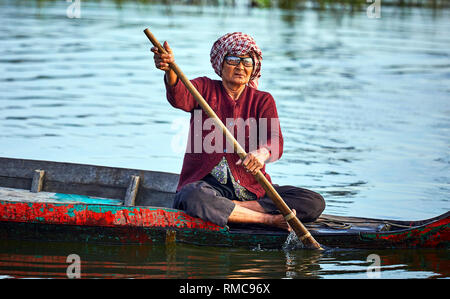 Tonlé Sap Lake,  Cambodia. 19th December, 2017. An old lady wearing eye glasses rows her wooden boat in a floating village on Tonlé Sap Lake. - Stock Photo