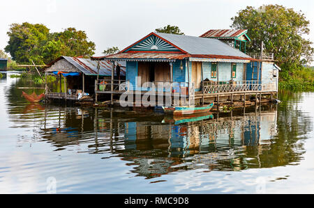 Tonlé Sap Lake,  Cambodia. 19th December, 2017. Colorful floating house with trees behind and a wooden boat in front. Photo: Bryan Watt - Stock Photo