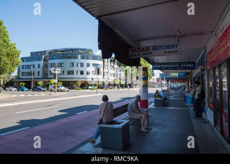 People wait at a bus stop near a set of traffic lights on Botany Road in the shopping area of the Sydney suburb of Mascot - Stock Photo