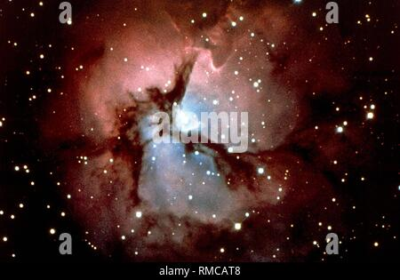 The Trifid Nebula (M 20 or NGC 6514) belongs to the constellation of the Sagittarius in our Milky Way galaxy. It contains both red emission nebulae and blue reflection nebulae. It seems to be divided by dark gaps, hence the name ('divided into three lobes'). Undated photo, probably from the 1980s. Stock Photo