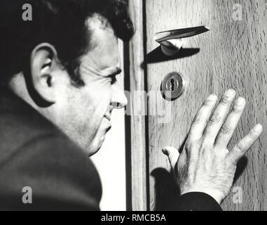 A curious man looks through the keyhole. - Stock Photo