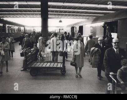 Series of the historical Muenchen Hauptbahnhof, October 1971. Crowded platform after the arrival of a train. - Stock Photo