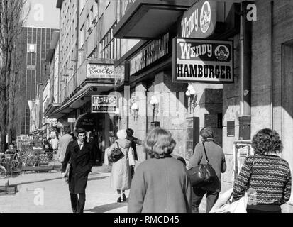 Passers-by on the Leopoldstrasse in Munich. Among others, they pass by the famous ice cream parlor 'Cafe Rialto' and 'Wendy'. - Stock Photo