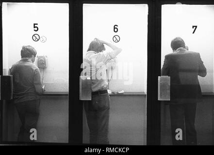 Three men are talking in cabins with public payphones, presumably in a post office. - Stock Photo
