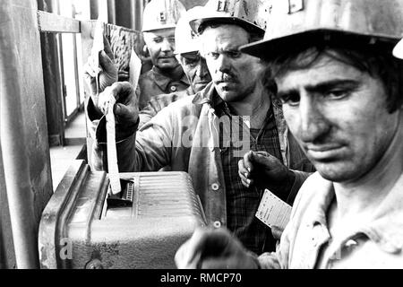 Mining worker of the coal mine 'Ruhrkohle AG' at the time clock during a shift change. - Stock Photo