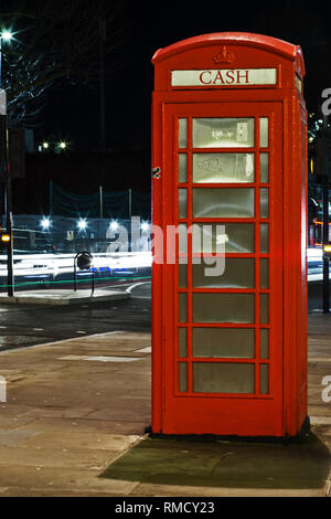 A classic Victorian red telephone box converted into a cash ATM machine by night - Stock Photo