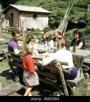 A family takes a break from hiking on a mountain pasture. - Stock Photo