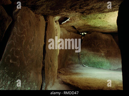 Megalithic art inside Mané Lud Neolithic passage grave, Morbihan, Brittany, France. Yokes on a passage stone & a 'figurine' in the burial chamber. - Stock Photo
