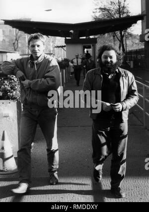 After the fall of the Berlin Wall, numerous East Berliners visit West Berlin. Here, two East Berliners in front of the last checkpoint at the Invalidenstrasse border crossing on their way to the West. - Stock Photo