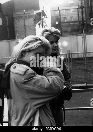 After the fall of the Berlin Wall, numerous East Berliners visited West Berlin. Here, two crying women in front of the last checkpoint at the border crossing in Invalidenstrasse. - Stock Photo