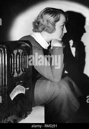 A young women listens to the radio. Advertising shot. Undated picture. - Stock Photo