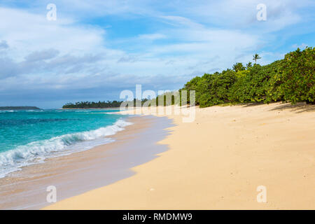 Shore of an azure, turquoise, blue lagoon. Waves, surf, swash at a remote empty idyllic sandy beach on Foa island, Haapai islands or Ha'apai group, To - Stock Photo