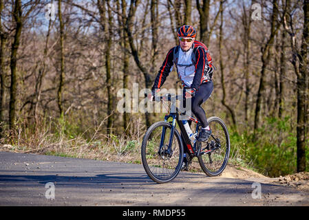 Sports cyclist rides along a trail in the forest on a spring sunny day. - Stock Photo